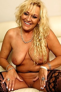 Busty blonde cougar Andrea two fingers deep on the sofa.