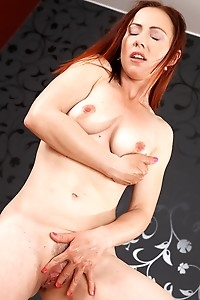 Mature redhead Violet Jones fingering herself on the sofa.